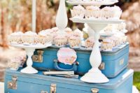 a retro-inspired dessert bar with blue suitcases and cupcakes on stands is a gorgeous idea for a retro wedding