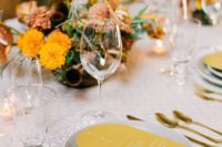 a retro-inspired wedding table setting done with mustard and grey touches, gold cutlery and bold centerpieces