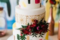a retro wedding cake with terrazzo patterns, gold detailing and bright blooms