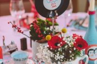 a retro wedding centerpiece with colorful candles in teacups, florals in teapots and a vinyl table name