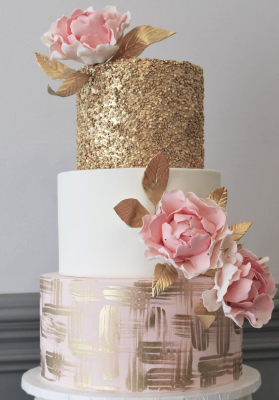 a romantic wedding cake with a gold, white and blush tier, pink sugar blooms with leaves
