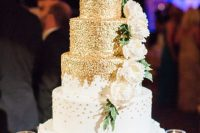 a romantic wedding cake with gold polka dot tiers and a white floral one, with sugar blooms and leaves