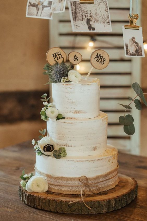 a semi naked wedding cake with white blooms and greenery, thistles, wood slices and burlap is a lovely idea for a rustic wedding
