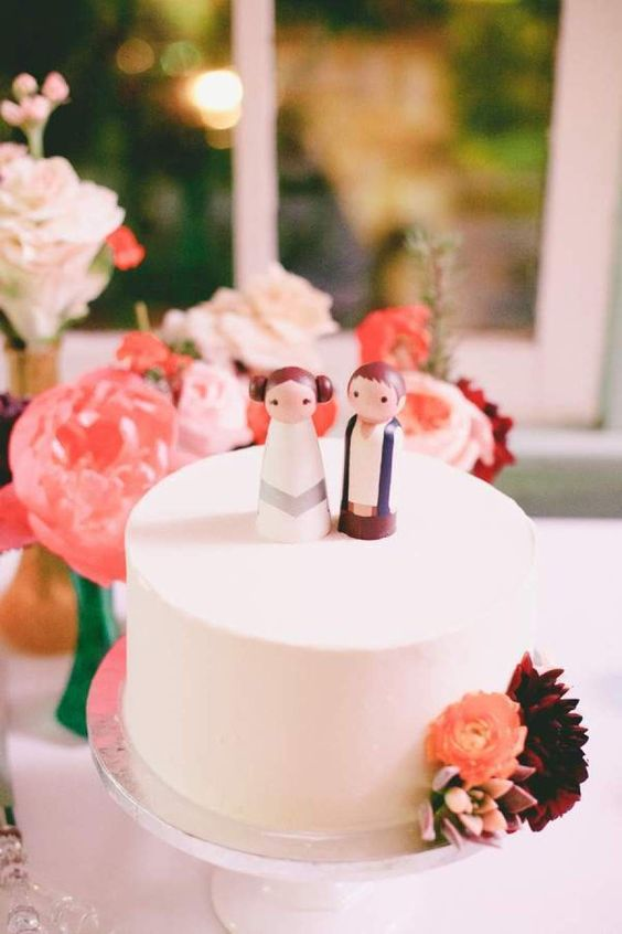 a sleek white buttercream wedding cake topped with wooden dolls showing famous Star Wars characters is a cool idea for a geeky wedding