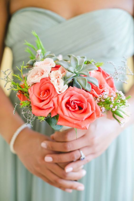 a small wedding bouquet with coral and blush blooms, greenery and succulents is very chic