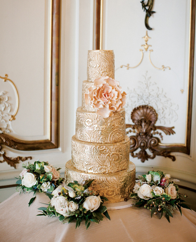 a sophisticated gold patterned wedding cake with a blush sugar bloom is a very spectacular and chic idea