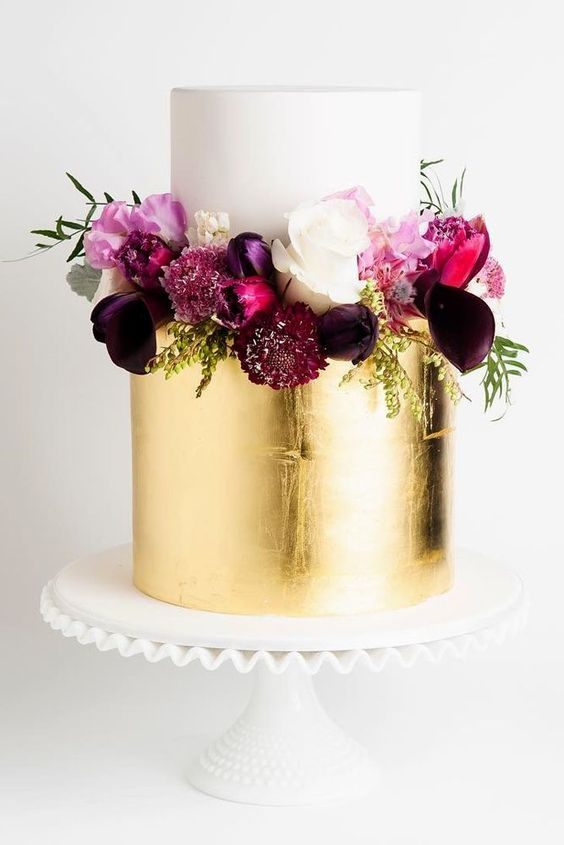 a sophisticated wedding cake with white and gold leaf tiers and purple, fuchsia and pink blooms and greenery