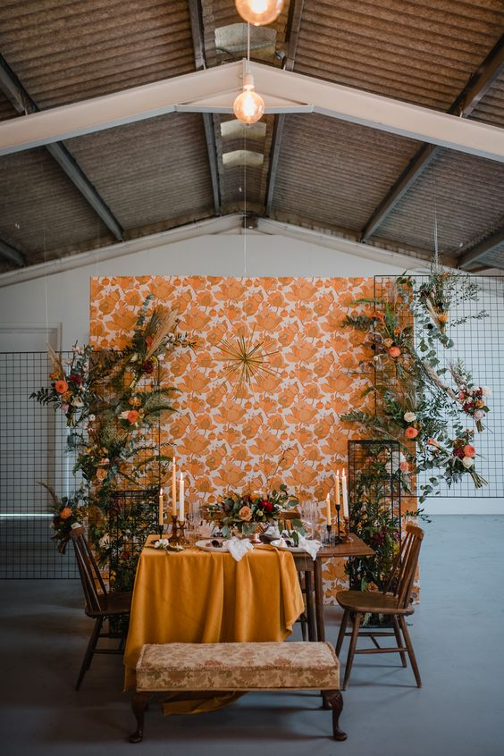 a stylish 70s inspired tablescape with a mustard tablecloth, yellow candles, florals and greenery plus a printed wallpaper backdrop
