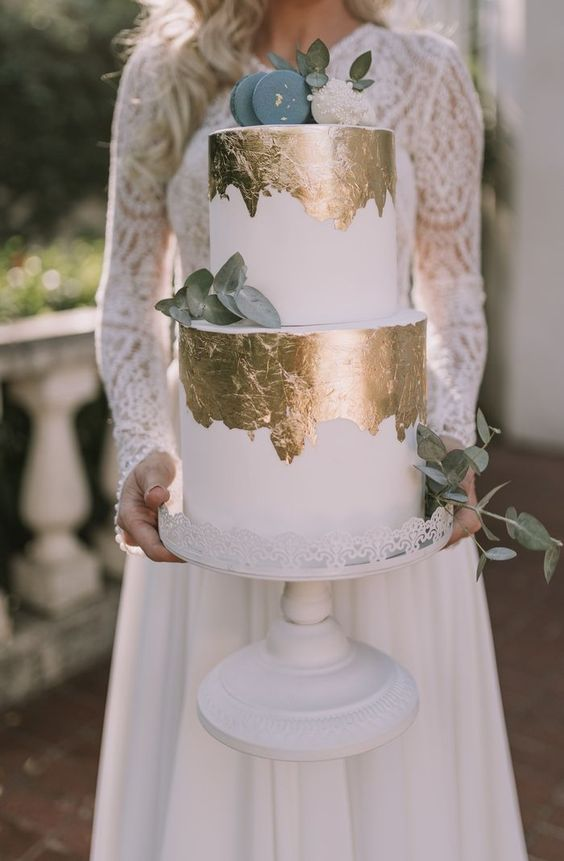 a stylish modern white wedding cake with gold leaf, eucalyptus, blue macarons and leaves on top