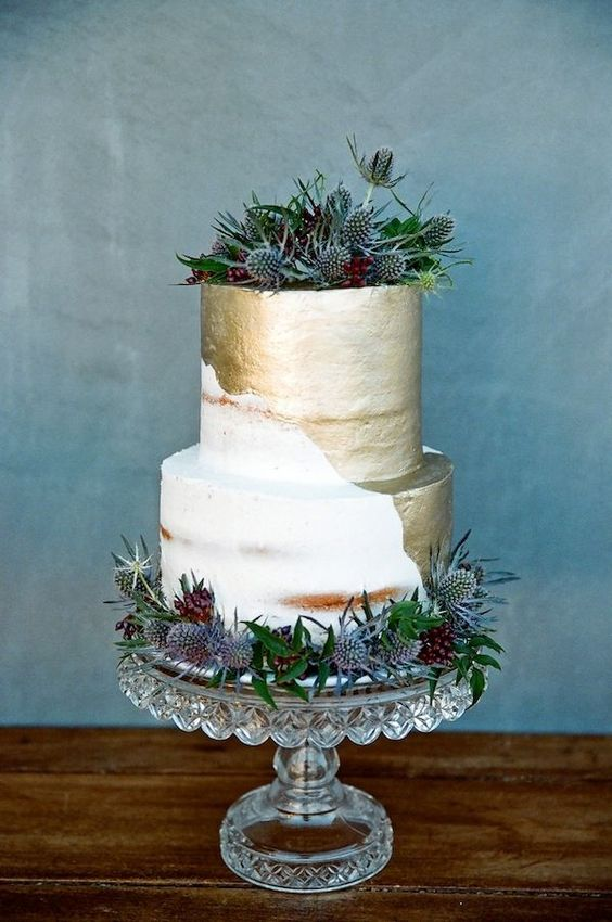 a stylish naked and gold leaf wedding cake with greenery and thistles is a bold trendy dessert