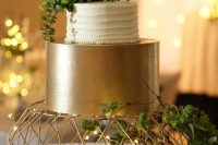 a stylish wedding cake with a white textural tier and a shiny gold one, with succulents on top is wow