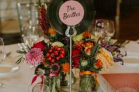 a stylish wedding centerpiece with a wood slice, colorful blooms, a vinyl table name for a retro meets rustic wedding