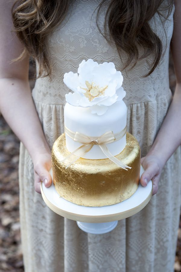 a stylish white and gold leaf wedding cake with a ribbon bow and a white sugar flower on top