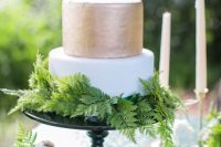 a stylish woodland wedding cake with a gold and white tier and lots of ferns covering the bottom