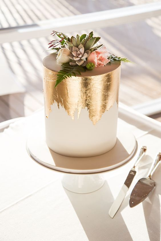 a tall white wedding cake with gold leaf decor, pastel blooms and succulents is very chic