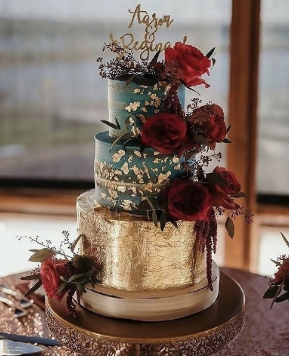a teal and gold leaf wedding cake with burgundy blooms and a calligraphy topper for a super bold wedding
