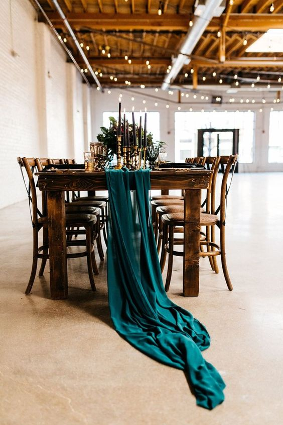 a teal fabric table runner, black candles, gold touches and greenery will make the tablescape moody and chic