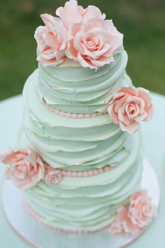 a textural mint wedding cake with a gold edge and pink sugar blooms looks very pretty and delicious