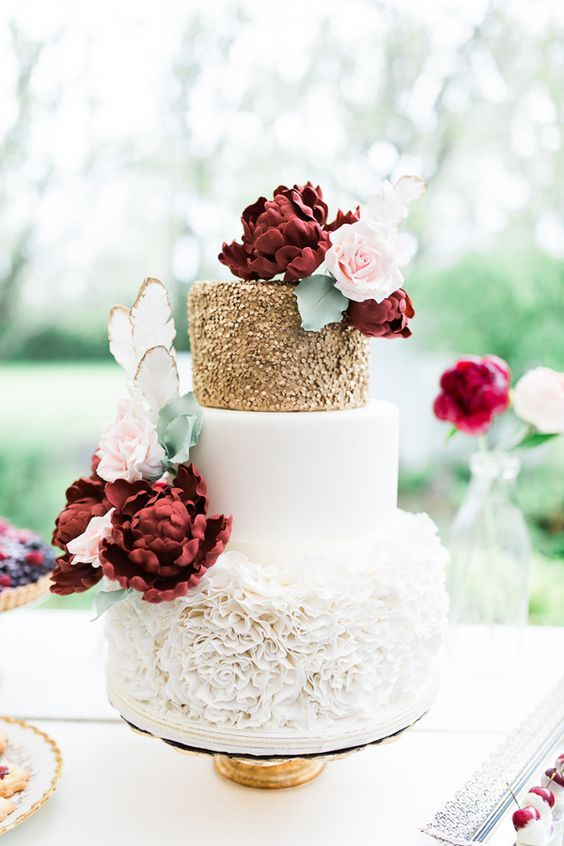 a very romantic and chic wedding cake with a sleek white, gold polka dot and white floral tier and lots of sugar blooms in burgundy and blush