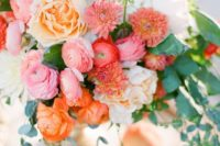 a warm-colored wedding centerpiece in peachy, pink, white and with some greenery cascading