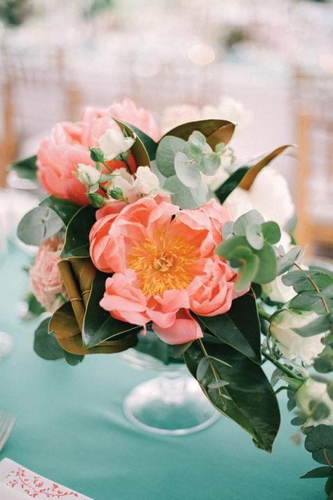 a wedding centerpiece with greenery, magnolia leaves, eucalyptus and coral and white blooms is amazing