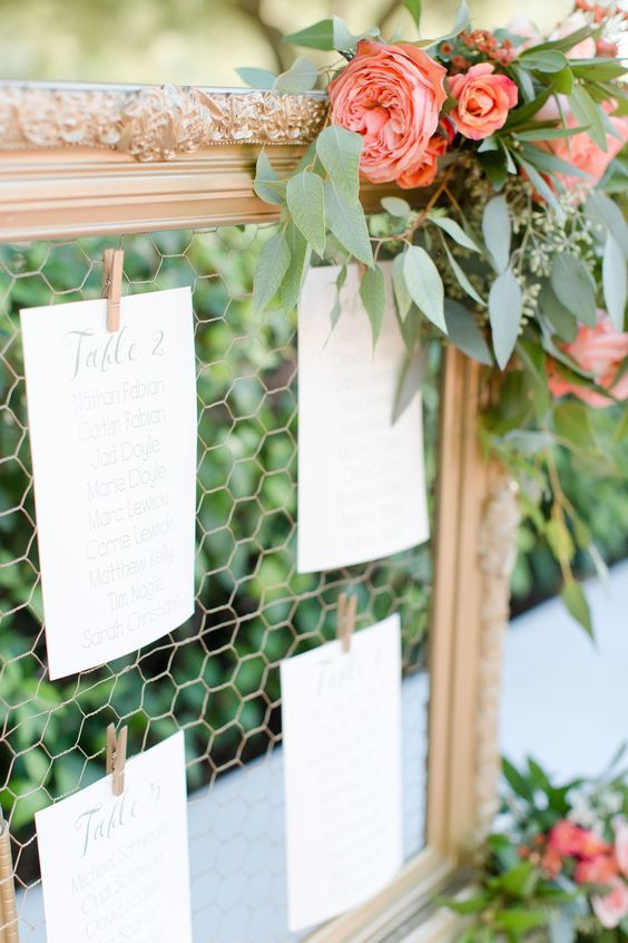 a wedding seating chart with gold frames, greenery and coral poenies looks very pretty and very fresh
