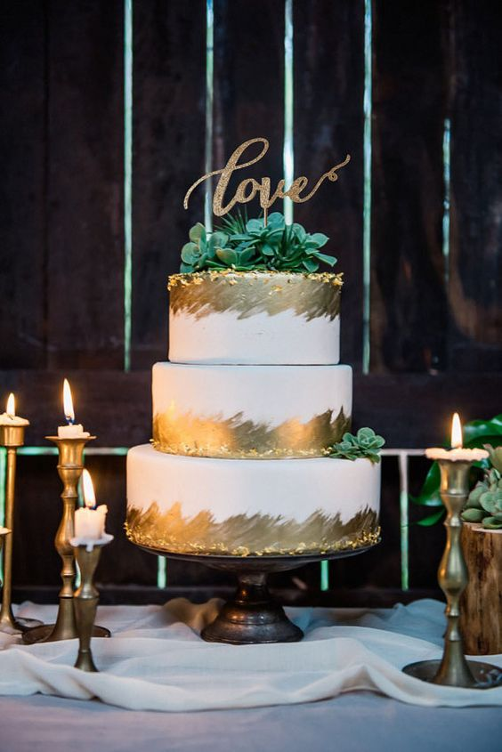 a white and gold wedding cake, with sugar succulents and olg leaf, with a gold glitter calligraphy topper