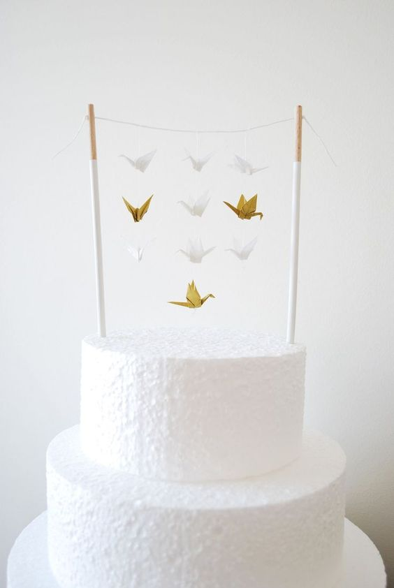 a white buttercream wedding cake with a stand and lots of small white and gold paper cranes hanging down from it is a very cute idea