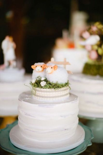 a white buttercream wedding cake with a unique cake topper - a couple of sheer on green grass is very cute and very lovely