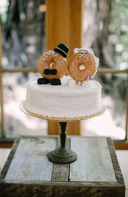a white buttercream wedding cake with cool donut cake toppers showing a bride and a groom is a very cheerful and laid-back idea