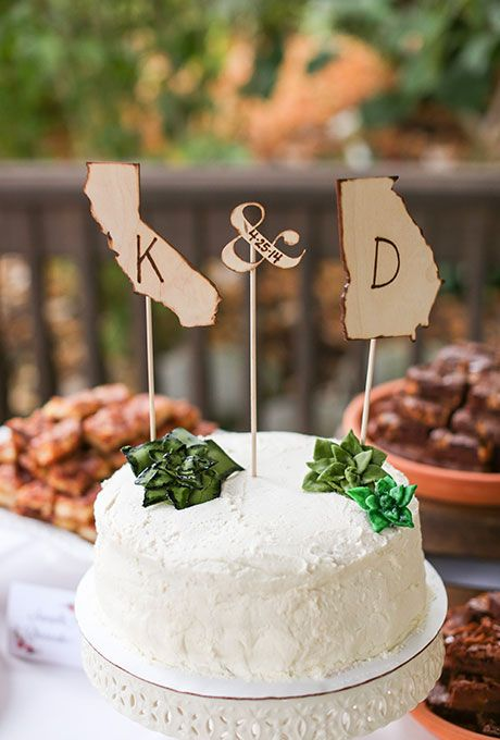 a white buttercream wedding cake with sugar succulents and plywood statement silhouettes that show where the couple comes from