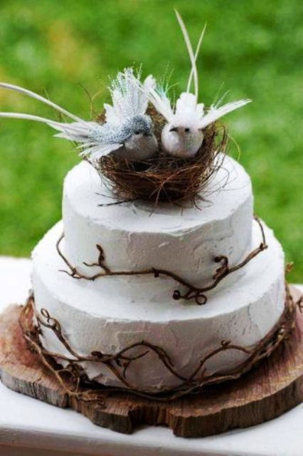 a white buttercream wedding cake with twigs and a nest with fake birds and feathers is a pretty rustic or woodland wedding cake idea