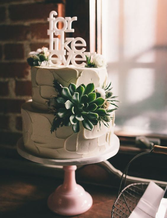 a white textural buttercream wedding cake decorated with a succulent, thistles and white blooms plus a white cake topper is amazing