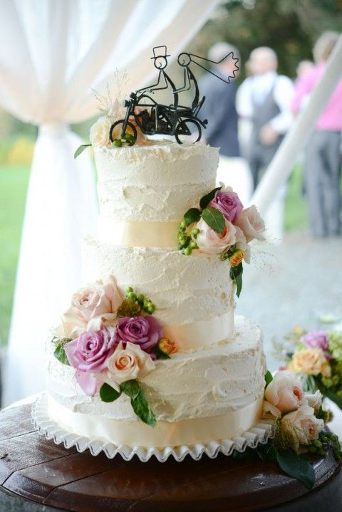 a white textural buttercream wedding cake with blush and hot pink blooms, leaves and berries plus a wire cake topper showing a couple riding a bike