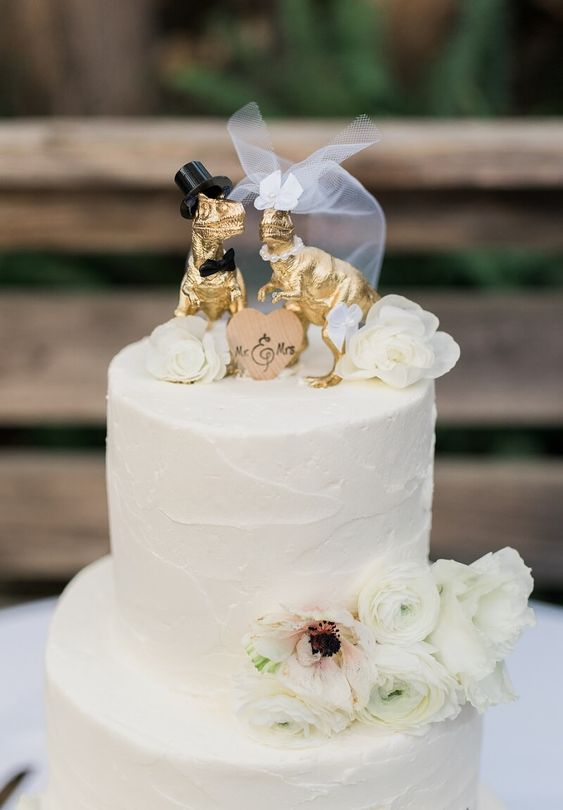 a white textural buttercream wedding cake with fresh white blooms and gilded dinosaur cake toppers showing a marrying couple