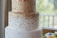 a white wedding cake covered with gold polka dots and a coral sugar bloom on top