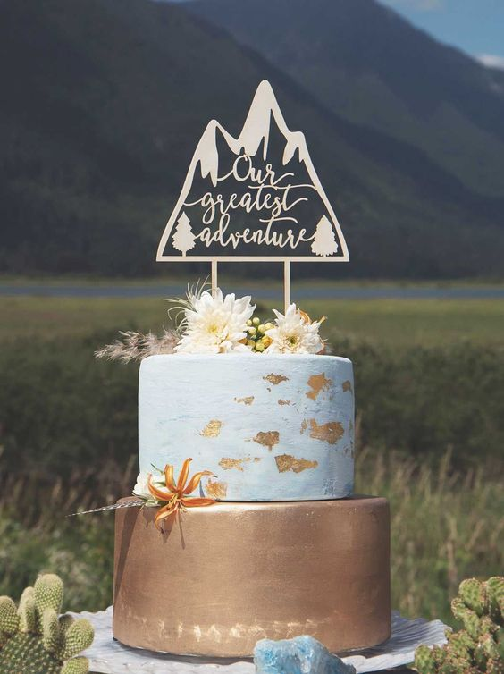 an adventure-themed wedding cake with a gold tier and a white one with gold leaf, fresh blooms, grass and a plywood cake topper