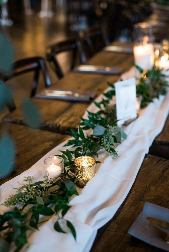 an airy white fabric table runner paired with a eucalyptus one and votives is a timeless idea to rock