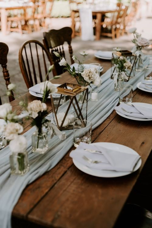 an aqua fabric table runner and neutral linens and blooms create a fresh and romantic spring wedding tablescape