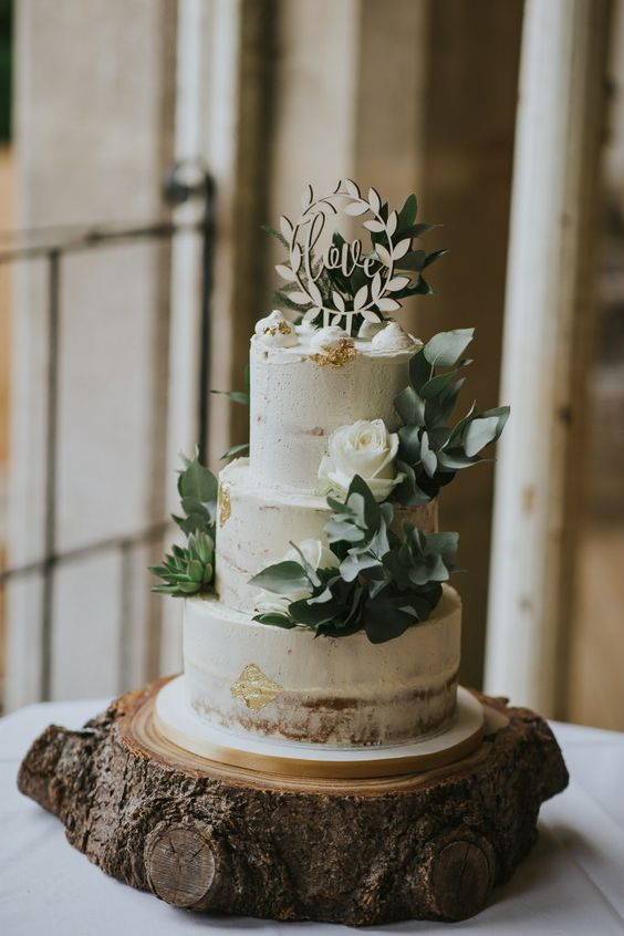an elegant naked rustic wedding cake with gold leaf, leaves, white roses, meringues and a plywood wreath cake topper is a very cool idea