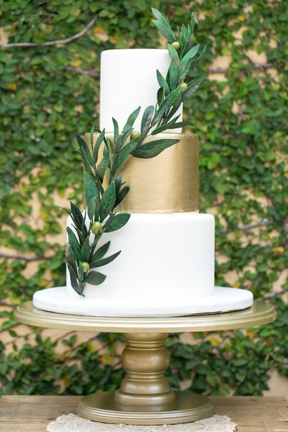 an elegant white and gold wedding cake with an olive branch is very chic and very modern