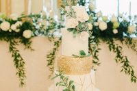 an ethereal wedding cake with white, a geometric gold and white and a gold polka dot tier, white blooms and greenery