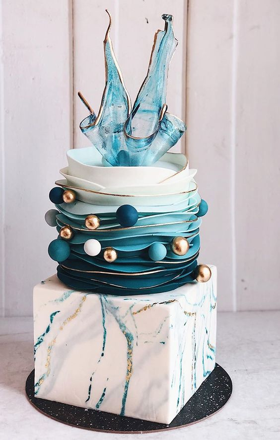 an outstanding wedding cake with a blue and gold marble cube tier, an ombre buttercream tier, blue, white and gold balls, a fantastic sheer splash cake topper