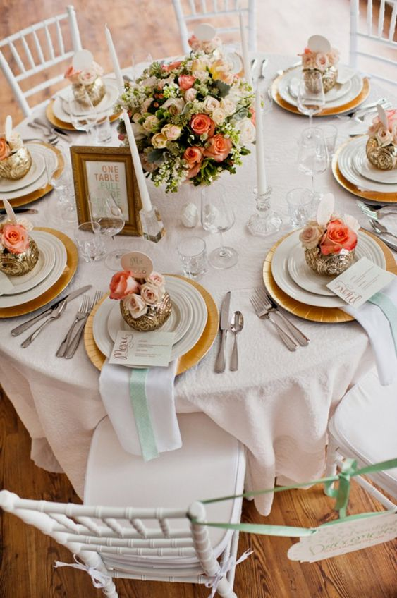 coral, peach and gold wedding tablescape with floral arrangements, white candles and white napkins with mint ribbons