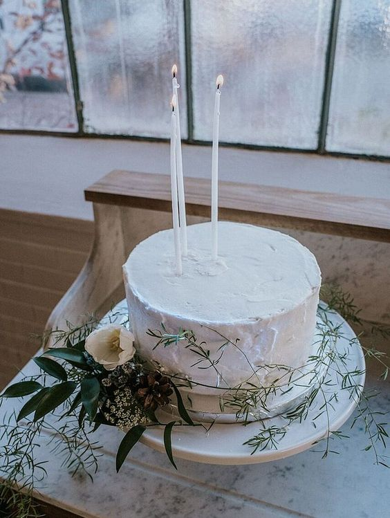 forget usual cake toppers for go for tall and thin candles, greenery and white blooms to make your wedding cake very chic and refined