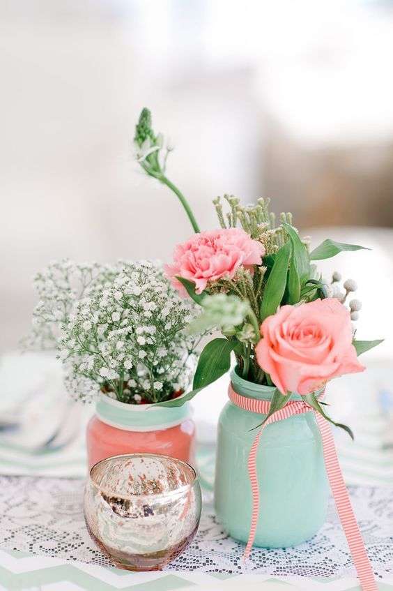 mint and coral jars with baby's breath, coral blooms and greenery to compose a cool wedding centerpiece