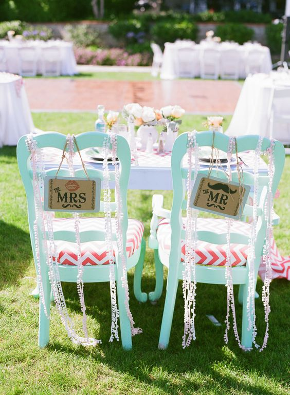 mint chairs with coral and white chevron seats, pompoms and signs for the couple