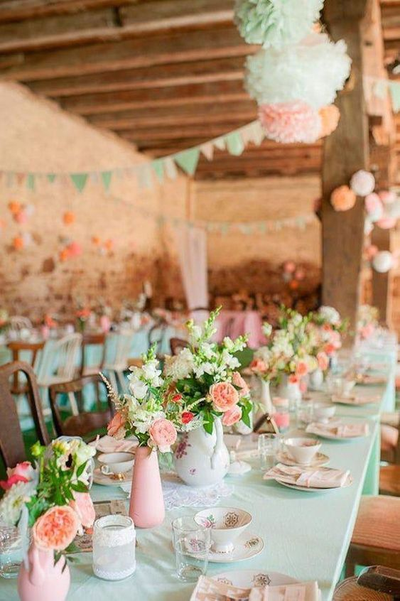 mint tablecloths, pink vases, coral and white blooms and greenery, paper pompoms and garlands