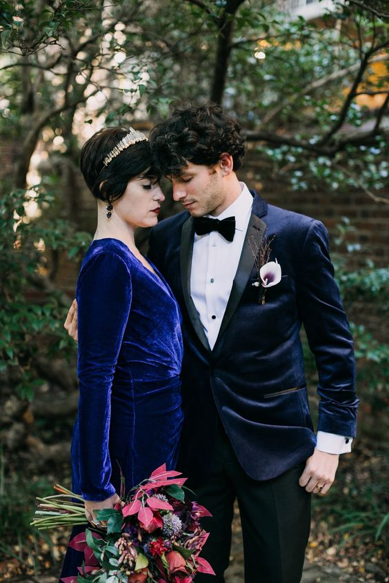 a Goth inspired groom's look with a midnight blue velvet tux with black lapels, a black bow tie and pants and a calla boutonniere