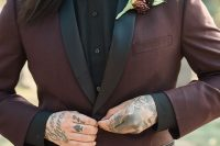 a Halloween groom's look with a black shirt and a leather bow tie, a burgundy tux with black lapels
